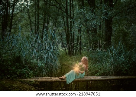 Witch sitting near  the river and practice witchcraft - stock photo