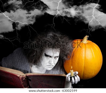 Witch with a magic book and pumpkin. Halloween theme. - stock photo