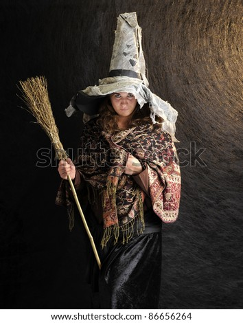 witch with broom on structured dark background - stock photo