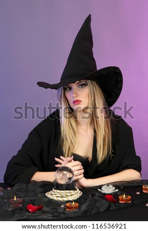 Witch with crystal ball. Fortune telling. On color background - stock photo