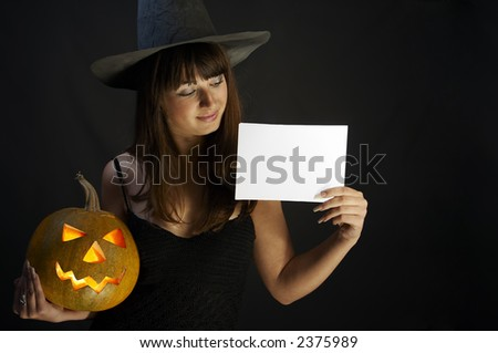 Witch with isolated white card and a pumpkin - stock photo