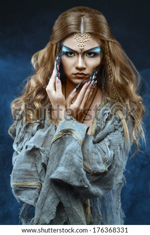 witch with long false nails with snakes  - stock photo