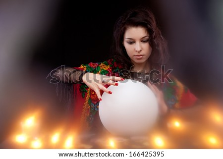Witch with magic crystal ball - stock photo