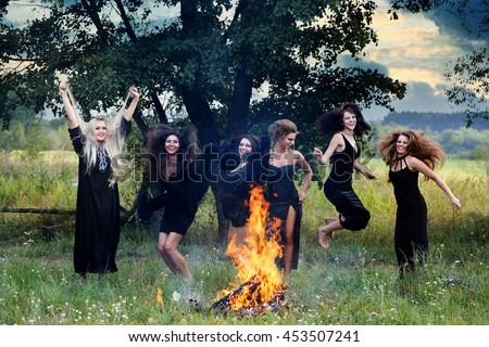 witches dancing near a campfire in the meadow