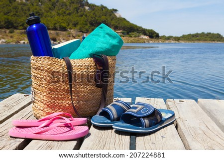 With a book and swimming suits on the wooden pier at the swimming lake - stock photo