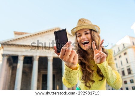 With a focal point on a woman's hand holding her digital camera as she is taking a selfie, smiling, and doing the victory sign, a woman tourist takes a photo of herself at the Pantheon in Rome. - stock photo