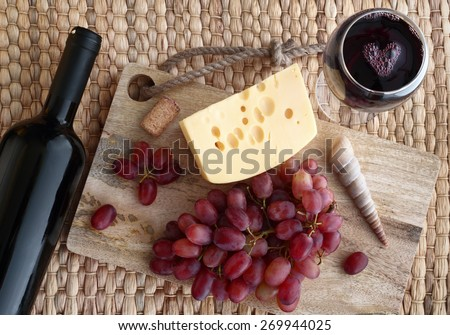 with a glass of wine, cheese and grapes on the table - stock photo