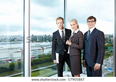 With employees in suits against the big window office - stock photo