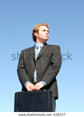 With jaw-jutting determination, a businessman, with both hands on the briefcase, looks to the future - stock photo