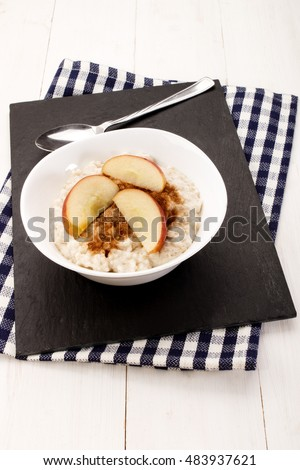 with milk boiled porridge, apple pieces, cinnamon and sugar in a white bowl