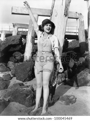 With sand between her toes, a young woman waves on the beach - stock photo