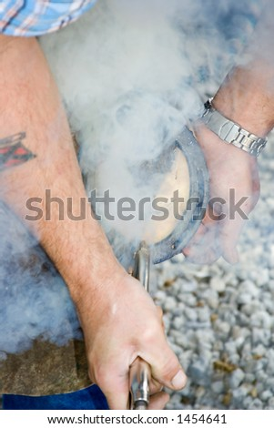 With the full shoe placed on the hoof, smoke arises, molding the shoe to the bottom of the hoof. Shallow dof - stock photo