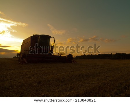 With the sun hanging low on the horizon, abandoned combine harvest wheat in the middle of a farm field. Morning yellow wheat field on the sunset cloudy orange sky background. - stock photo