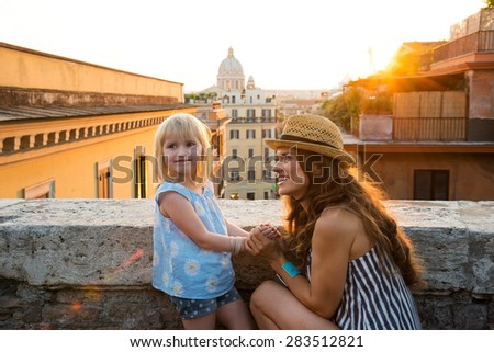 With views over Rome, a brunette mother wearing summer clothing and a hat is kneeling in front of her daughter, holding her hands, talking, and smiling. In the distance, St. Peter's Basilica. - stock photo