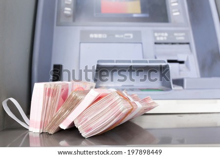 withdrawal a lot of CNY from the ATM - stock photo