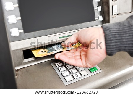 withdrawing money from an atm, collecting australian $50 notes, copy space on the screen. - stock photo