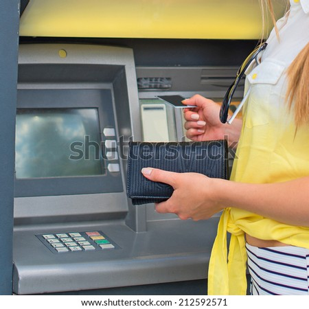 Withdrawing money from an ATM. Unrecognizable person. - stock photo