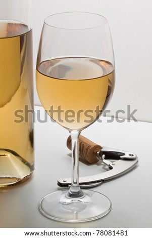 Withe wine in glass with bottle and corkscrew. - stock photo