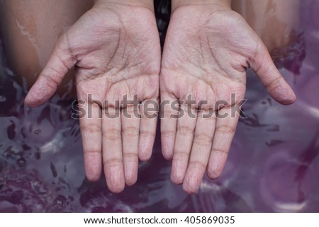 withered hands of young girl after swimming is long time - stock photo