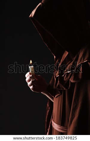 wizard in black cape with candle - stock photo