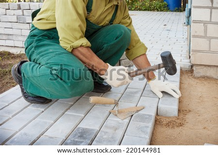 Wizard puts the blocks, making the sidewalk - stock photo