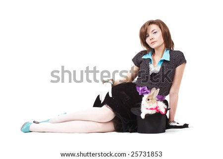 Wizard young female lying with rabbit in magic hat - stock photo