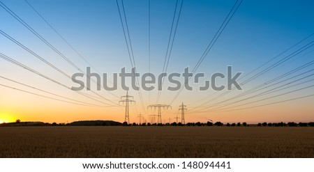 Wlwctric power lines and towers on the sunset - stock photo