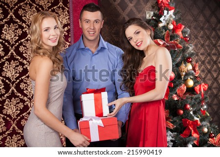 wo happy women and man holding gift boxes. smiling brunette and blond girls in red in front of christmas tree - stock photo