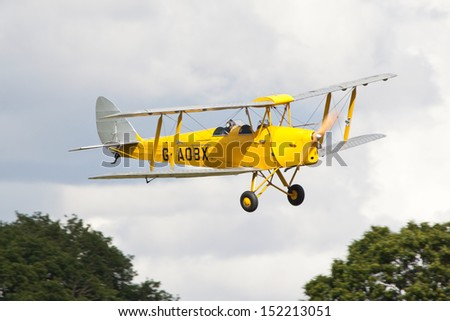 WOBURN ABBEY, BEDFORDSHIRE, UK - AUGUST 18: De Havilland DH.82A Tiger Moth flying on August 18, 2013 at the De Havilland Moth Rally, Woburn Abbey, Bedfordshire, UK.
