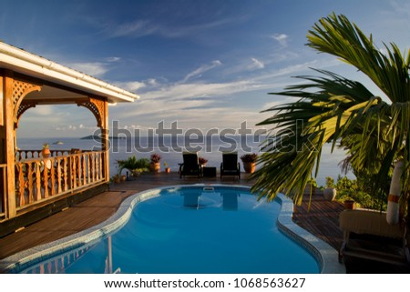 Wodden terrace with pool and ocean in the background