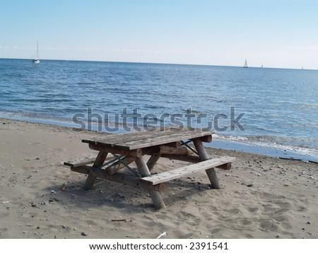 woden table on a sand beach - stock photo