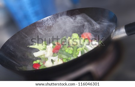 Wok cooking healthy asian food with vegetables and mushrooms - stock photo