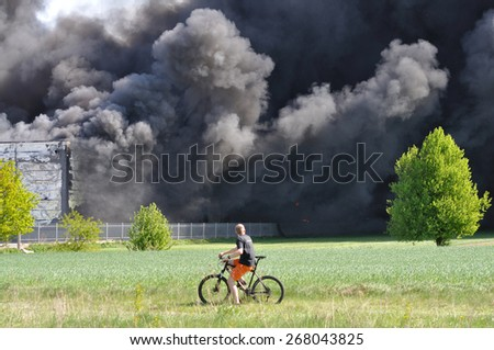 WOLKA KOSOWSKA, POLAND - MAY 10: An observer looking at the smoke of the burning China Mart storehouse, May 10, 2011 in Wolka Kosowska, Poland. The fire burned 150 storage units covering nearly 2 hect - stock photo