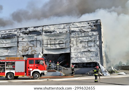 WOLKA KOSOWSKA, POLAND - MAY 10, 2011: Firefighters extinguish a raging fire in a China Mart storehouse. The fire burned 150 storage units covering nearly 2 hectares. - stock photo