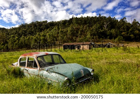 WOLLOMBI,AUSTRALIA - JUNE 10,2012: A vintage car sits abandoned in a field. Wollombi is a picturesque village 130km north of Sydney, in the wine-producing Hunter Valley region. - stock photo