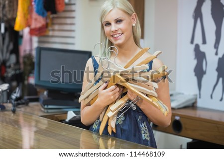 Woma standing behind counter holding hangers in boutique - stock photo
