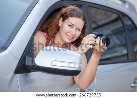 Woman a driver holding camera in hands while sitting inside the car - stock photo