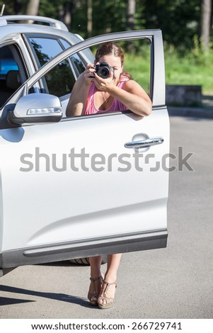 Woman a photojournalist using the car door to stabilize the camera shaking - stock photo