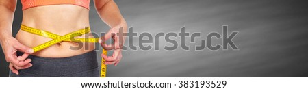 Woman abdomen with measuring tape over black background. - stock photo