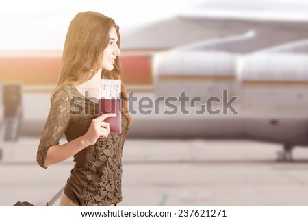 Woman about to board an airplane in an airport runaway at sunset - stock photo