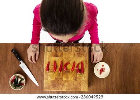 woman about to chop up chillis on a wooden chopping board taken from a birds eye view from above - stock photo