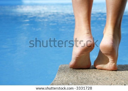 Woman about to dive into bright blue pool