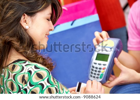woman about to enter the pin number after paying by credit card at a clothes store - stock photo