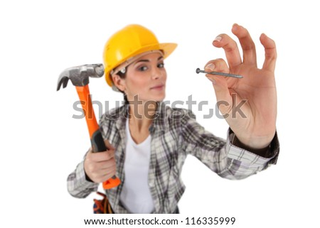 Woman about to hit nail with hammer - stock photo