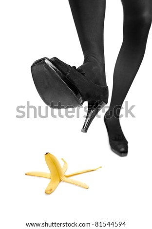 Woman about to step on a banana peel isoltaed on white background - stock photo