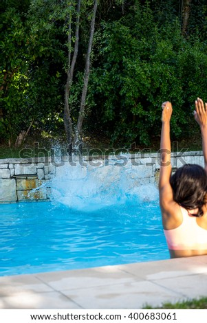 Woman about to swim in swimming pool on a sunny day - stock photo