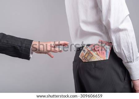 Woman about to take money out of back pocket of a businessman - stock photo