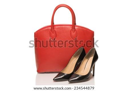 Woman accessories on white background, red handbag and black stileto - stock photo