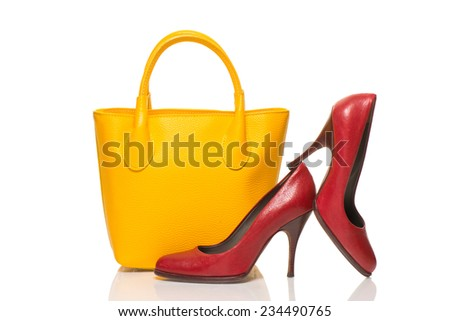 Woman accessories on white background, yellow handbag and red high heels