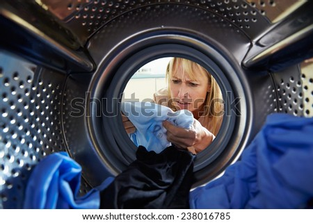 Woman Accidentally Dyeing Laundry Inside Washing Machine - stock photo